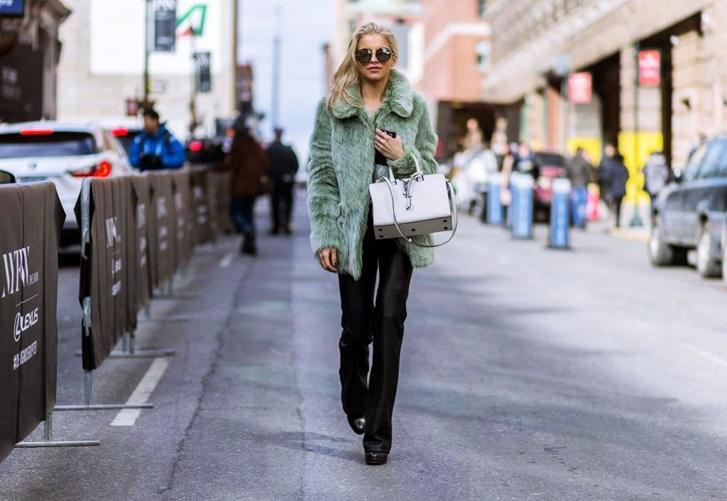 NEW YORK, NY - FEBRUARY 11: German fashion blogger Caroline Daur wearing a green Topshop Unique fluffy fur jacket, black Zara pants, black Poi Lei shoes, Jimmy Choo sunglasses and a white Yves Saint Laurent bag seen outside BCBG Max Azria during New York Fashion Week: Women