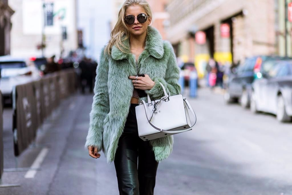 NEW YORK, NY - FEBRUARY 11: German fashion blogger Caroline Daur wearing a green Topshop Unique fluffy fur jacket, black Zara pants, Jimmy Choo sunglasses and a white Yves Saint Laurent bag seen outside BCBG Max Azria during New York Fashion Week: Women